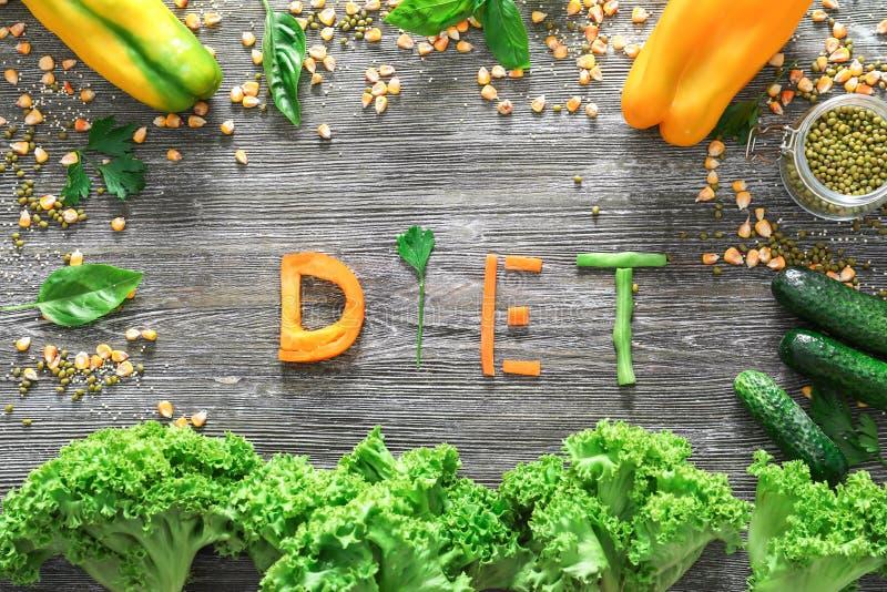 Zusammensetzung mit gesundem Gemüse und Wort DIÄT auf hölzernem Hintergrund lizenzfreies stockbild