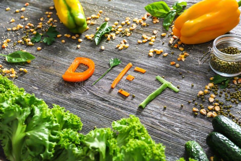 Zusammensetzung mit gesundem Gemüse und Wort DIÄT auf hölzernem Hintergrund stockfotografie
