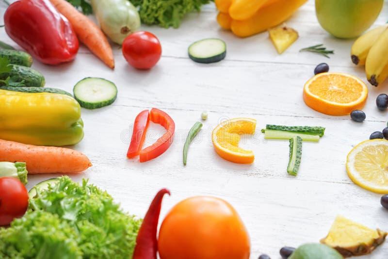 Zusammensetzung mit gesunden Produkten und Wort DIÄT auf hellem hölzernem Hintergrund stockbilder