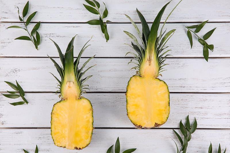 Zusammensetzung mit Hälften der reifen Ananas auf hölzernem Hintergrund lizenzfreie stockfotos