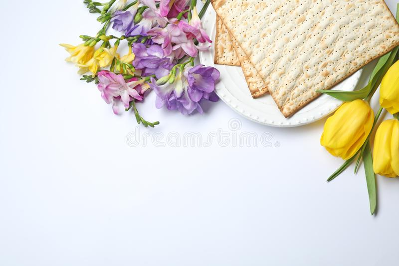 Zusammensetzung mit Matzo und Blumen auf weißem Hintergrund, Draufsicht stockbild