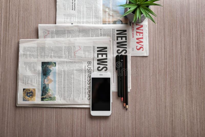 Zusammensetzung mit Morgenzeitungen und -telefon auf hölzernem Hintergrund stockbild