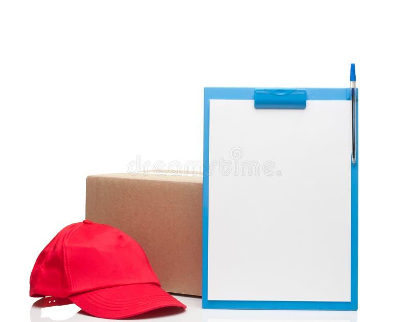 Zusammensetzung mit roter Kappe und Pappschachtel des Klemmbrettes lizenzfreie stockfotografie