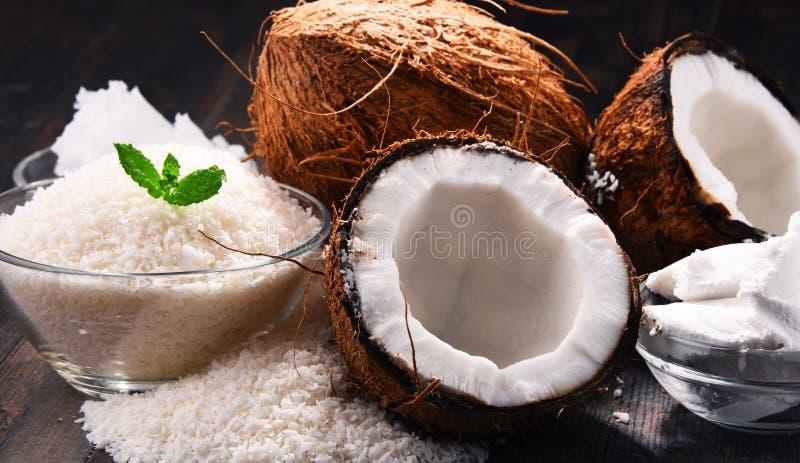 Zusammensetzung mit Schüssel zerrissener Kokosnuss und Oberteilen lizenzfreies stockbild