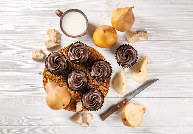 Zusammensetzung mit Schokoladenkleinen kuchen, Schale Milch und Birnen auf Holztisch stockfotografie
