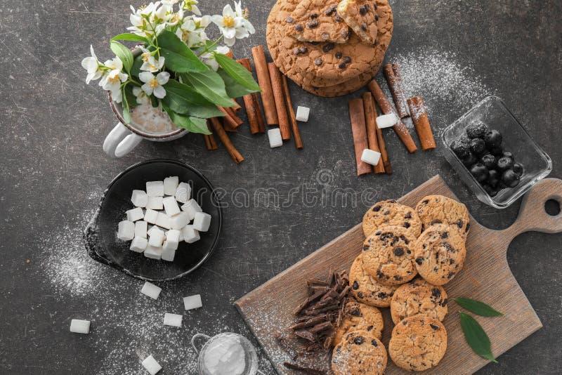 Zusammensetzung mit Schokoladensplitterplätzchen und -zucker auf grauem Hintergrund lizenzfreies stockbild