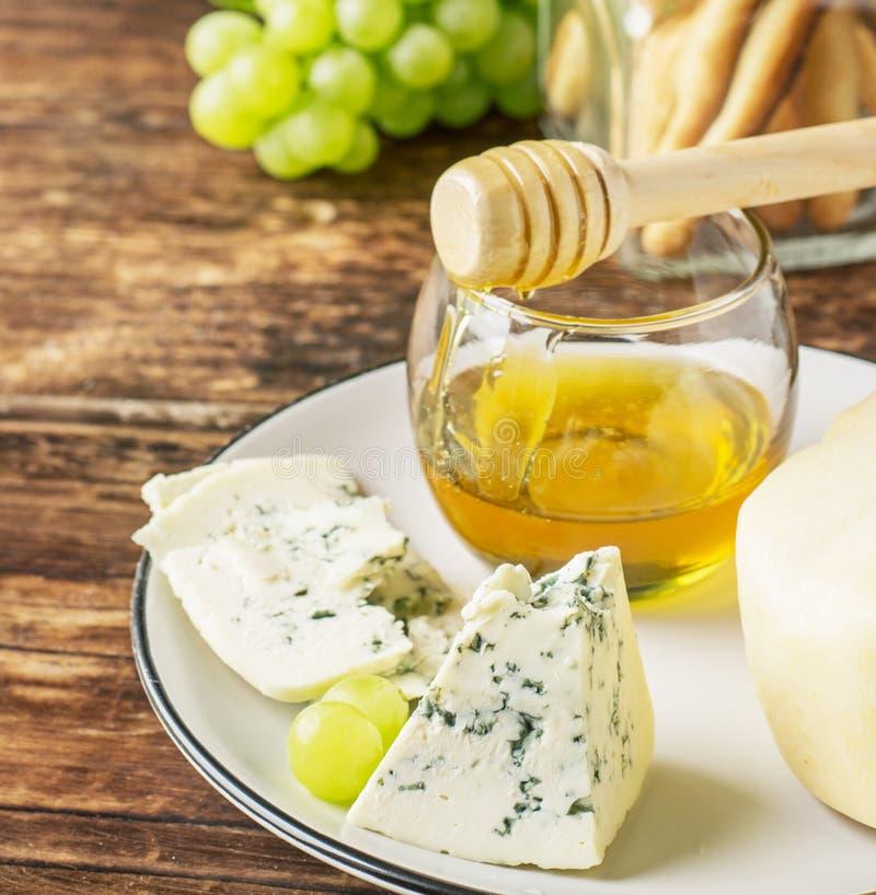 Zusammensetzung mit Traube, Käse und Honig stockfotografie