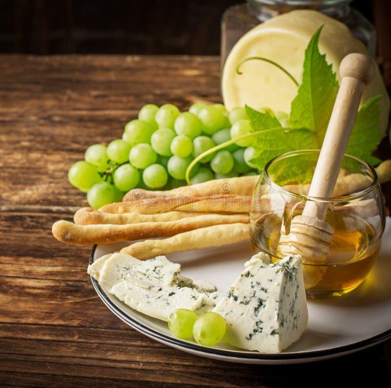 Zusammensetzung mit Traube, Käse und Honig lizenzfreie stockbilder