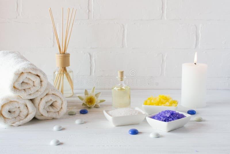 Zusammensetzung von Badekurort Wellnessprodukten auf weißem Hintergrund mit Tuch weiße Lilie, Seesalz, Badeöl, Zuckerkörperpeelin stockfotografie