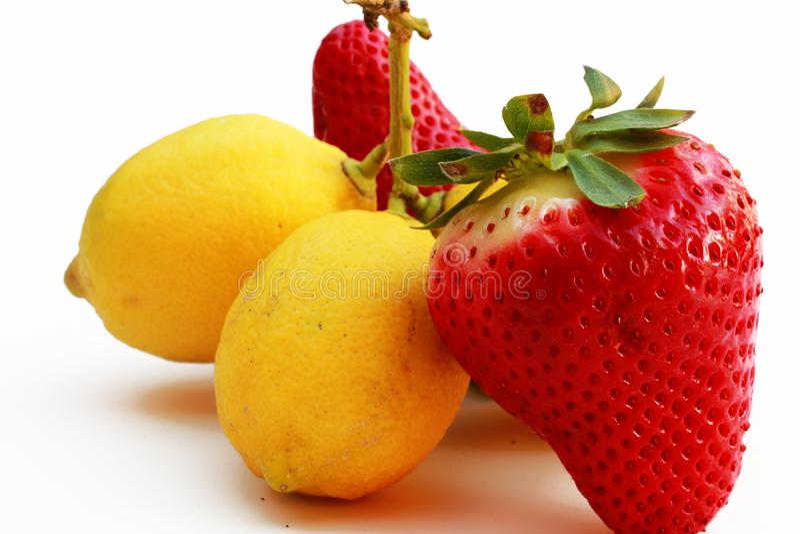 Zusammensetzung von den Erdbeeren und von Zitronen lokalisiert auf weißem Hintergrund lizenzfreie stockfotos