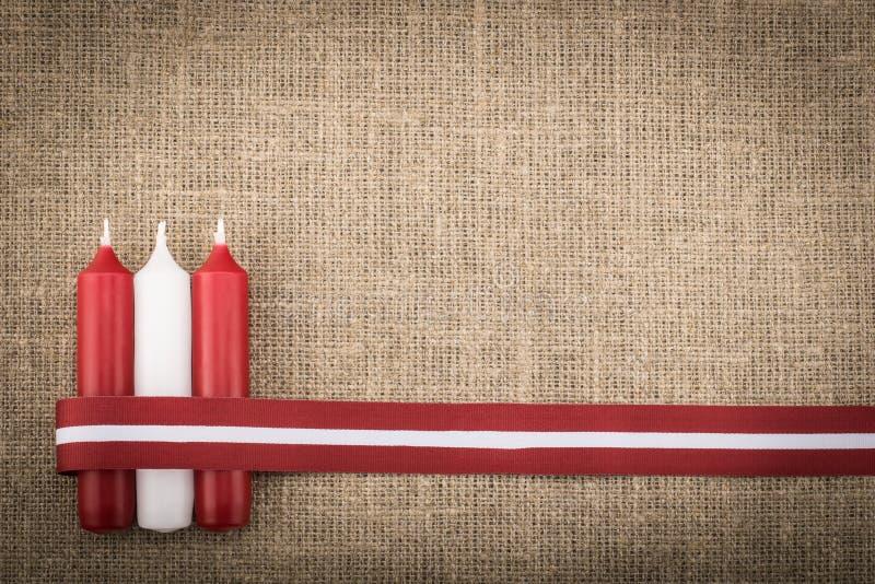 Zusammensetzung von drei roten weißen Kerzen und von lettischem Flaggenband stockfotografie