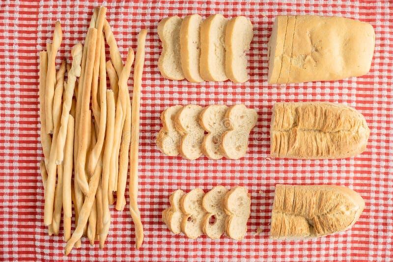 Zusammensetzung von Laiben und von breatsticks über roter und weißer Kontrolleurtischdecke mit Brot schneidet Ansicht von oben stockfotografie