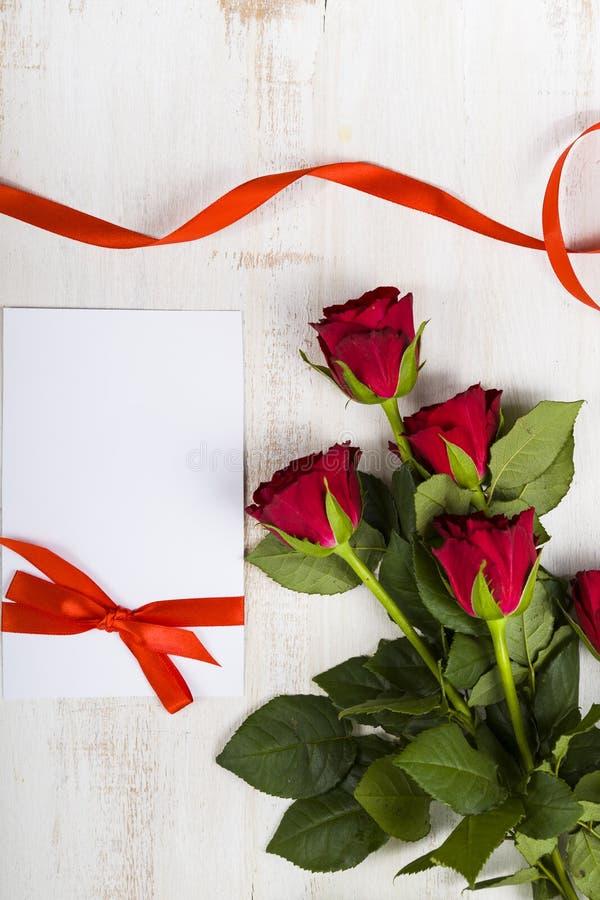 Zusammensetzung von roten Rosen, von Karte und von Band stockfotos