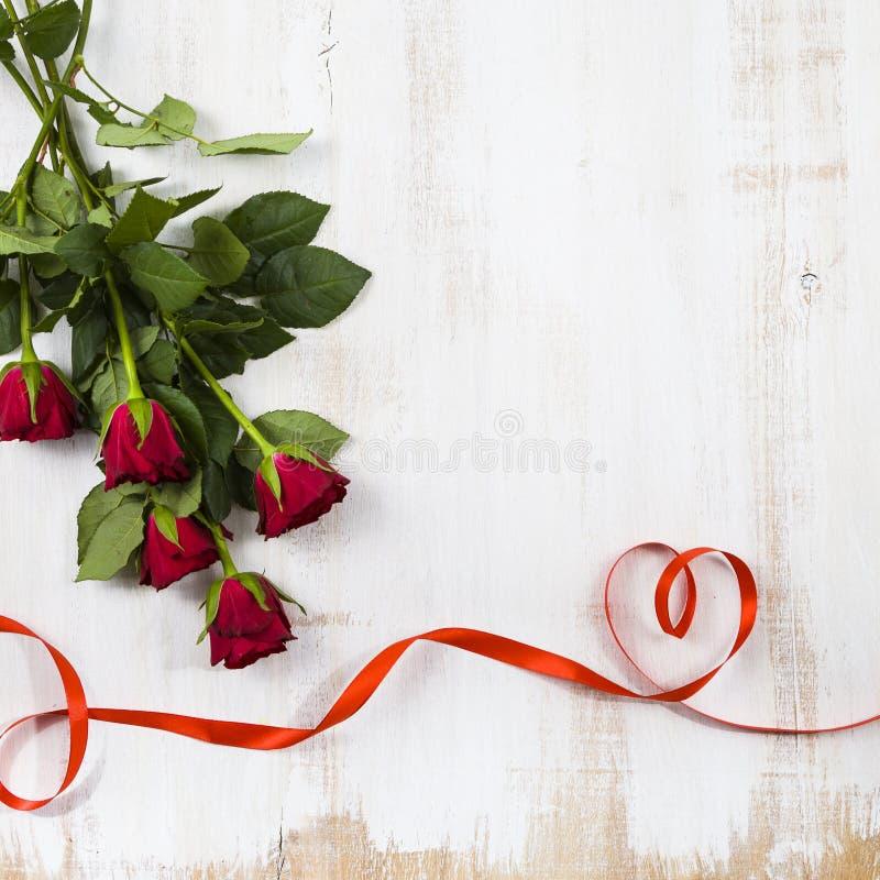 Zusammensetzung von roten Rosen und von Band lizenzfreie stockfotos