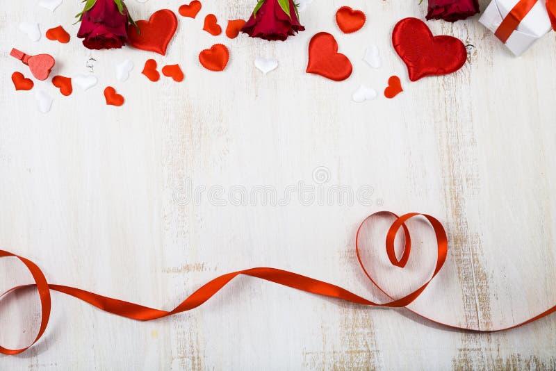 Zusammensetzung von roten Rosen und von Band lizenzfreies stockfoto