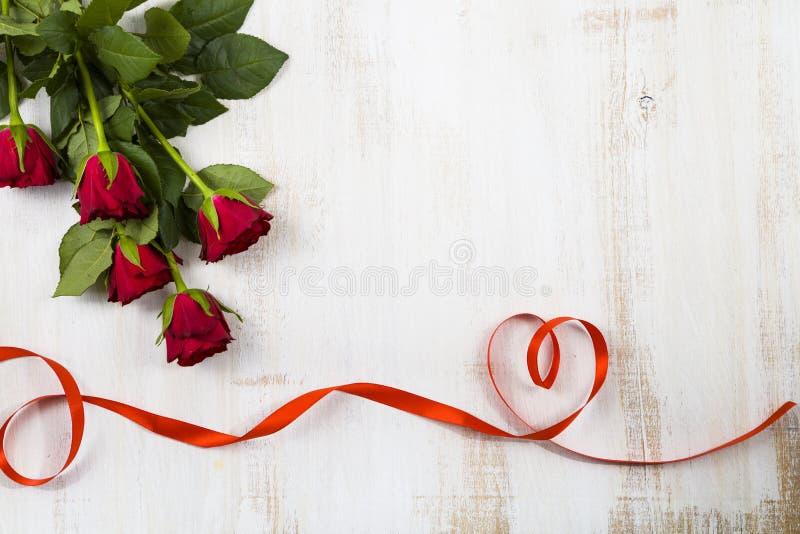 Zusammensetzung von roten Rosen und von Band stockfotos