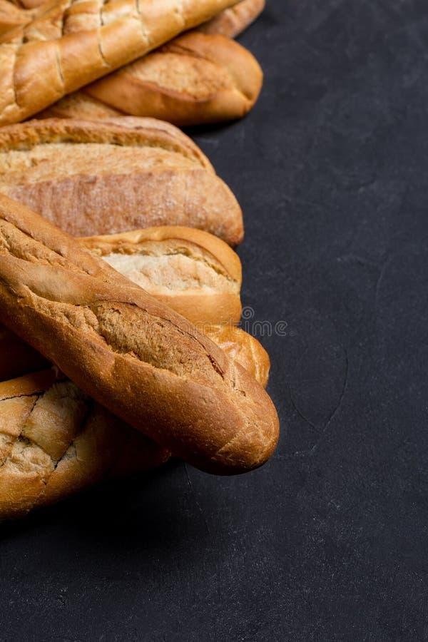 Zusammenstellung des frischen Brotes auf dunklem Hintergrund stockfoto