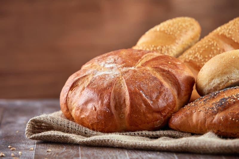 Zusammenstellung des gebackenen Brotes auf Holztischhintergrund stockfoto
