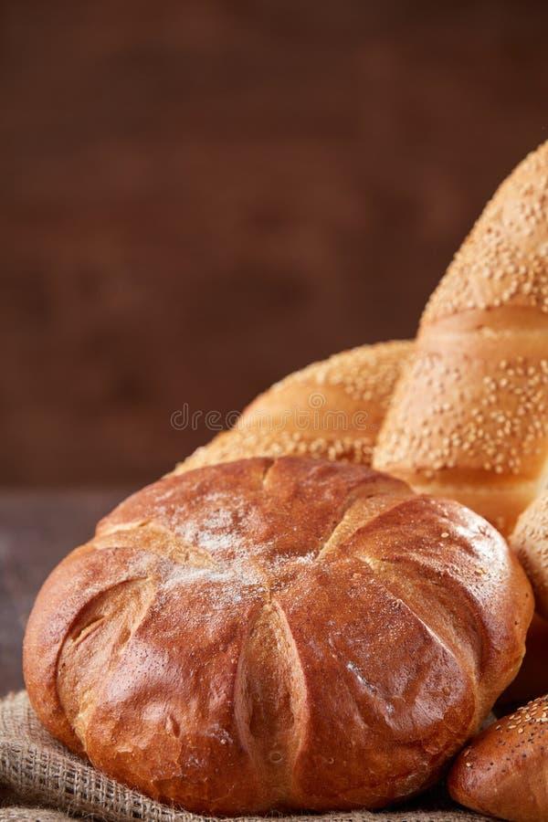 Zusammenstellung des gebackenen Brotes auf Holztischhintergrund stockbild