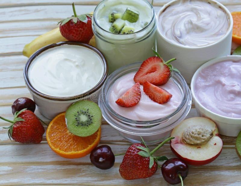 Zusammenstellung des unterschiedlichen Joghurts zum Frühstück mit Beeren lizenzfreie stockfotografie