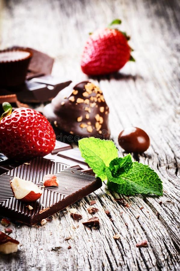 Zusammenstellung von feinen Schokoladen und von Pralinen mit frischer Erdbeere stockfotografie