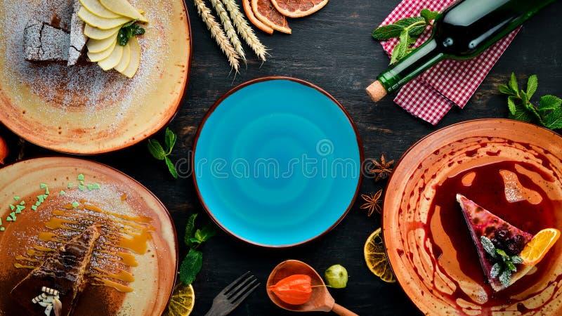 Zusammenstellung von Fruchtnachtischen und -backen auf einem Holztisch Strudel, Käsekuchen, Schokoladenkuchen, Eiscreme stockfotografie