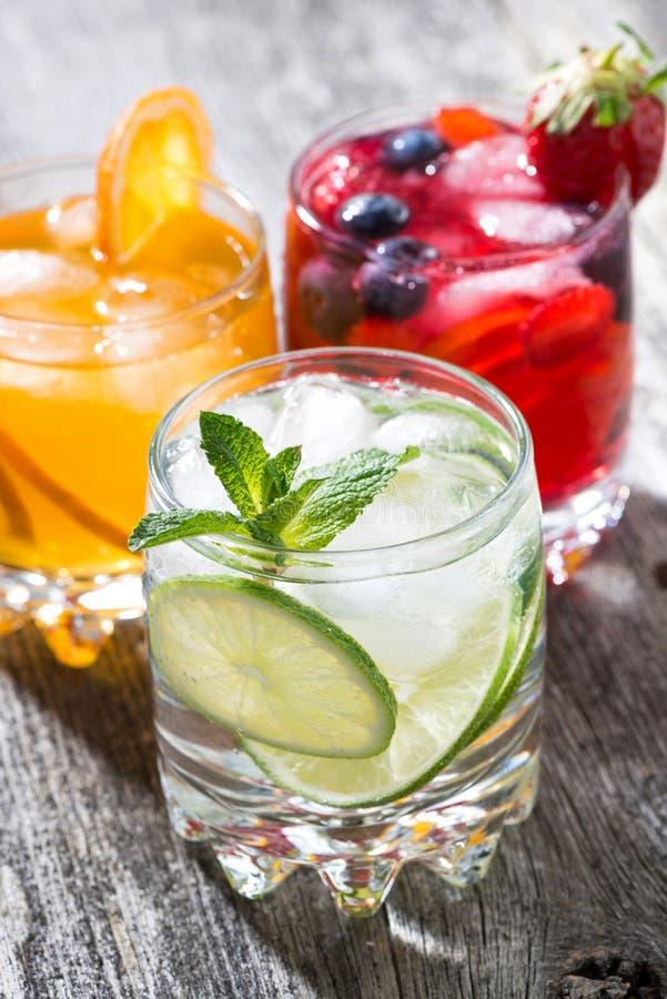Zusammenstellung von gefrorenen Fruchtgetränken auf hölzernem Hintergrund, vertikal lizenzfreie stockfotografie