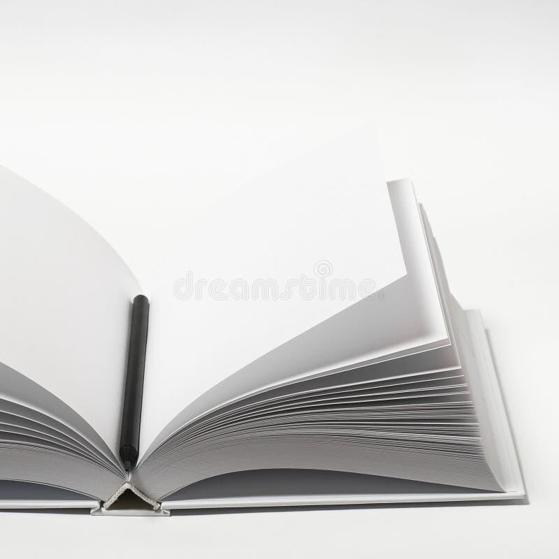 Zusammenstellung von geschlossenem leerem quadratischem Buch und schwarzem Bleistift auf weißem, texturiertem Papiergrund lizenzfreie stockbilder