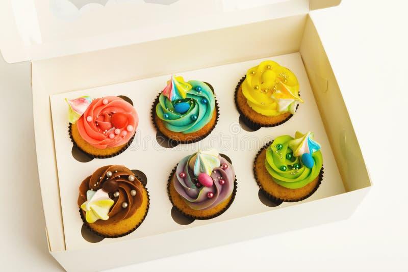 Zusammenstellung von geschmackvollen kleinen Kuchen mit bunten buttercream Oberteilen, auf Weiß stockfotografie