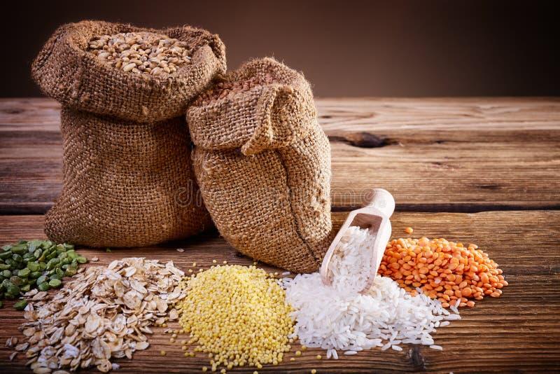 Zusammenstellung von Getreide auf einem Holztisch stockfotografie