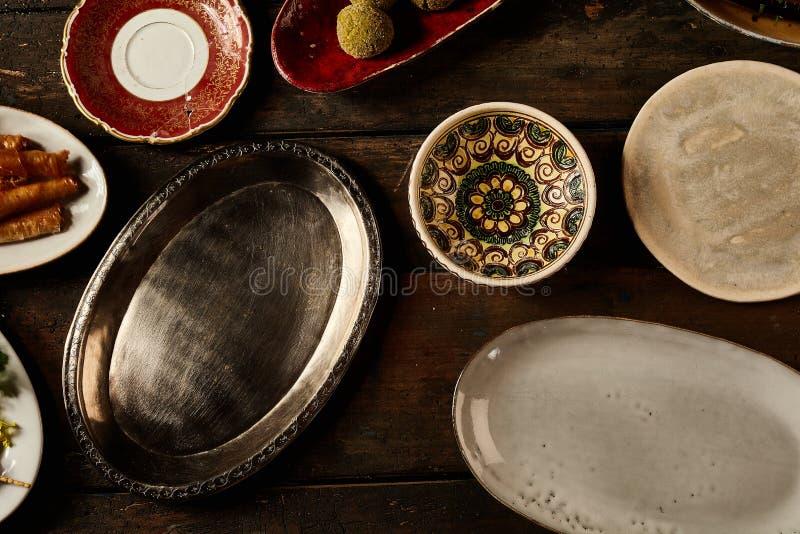 Zusammenstellung von leeren rustikalen Tellern auf einer Tabelle stockfoto