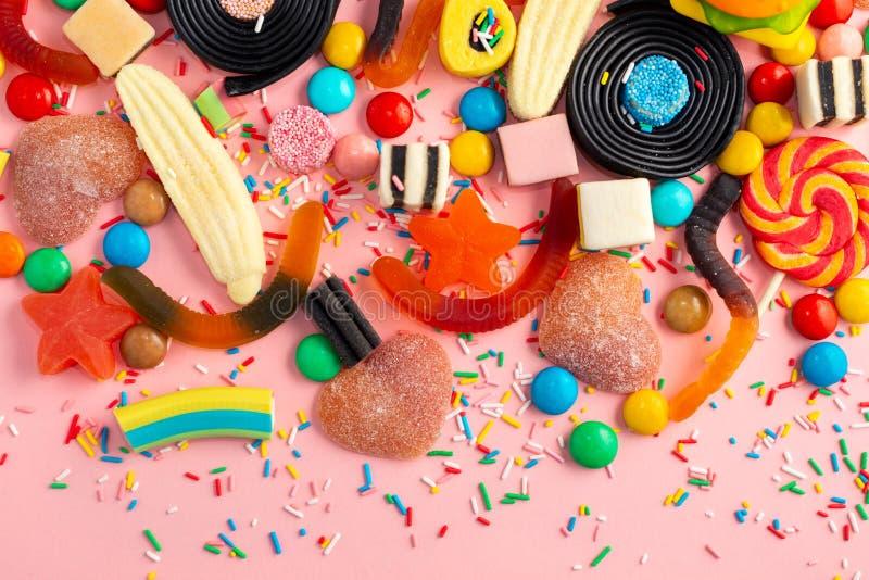 Zusammenstellung von Lutschern, tragen Bonbon, Süßigkeiten Früchte und besprühen auf Rosa wie Hintergrund, Kopienraum lizenzfreies stockfoto