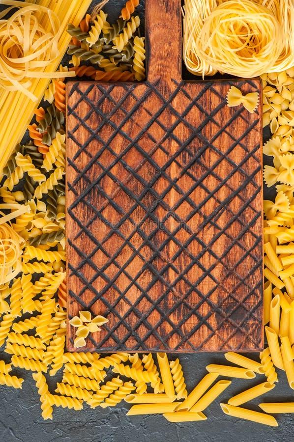 Zusammenstellung von rohen Arten und von Formen von italienischen Teigwaren und von hölzernem b lizenzfreie stockbilder