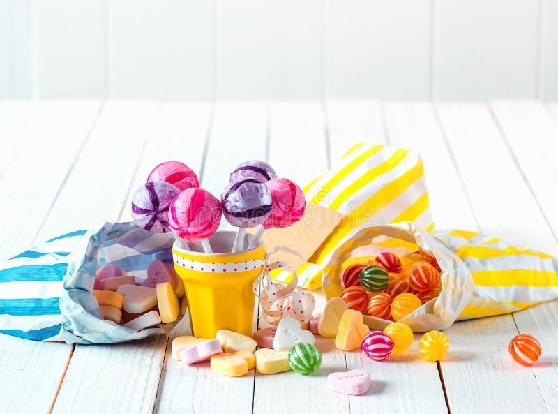 Zusammenstellung von Süßigkeiten in den Taschen und von Schale über einer Tabelle stockfotografie