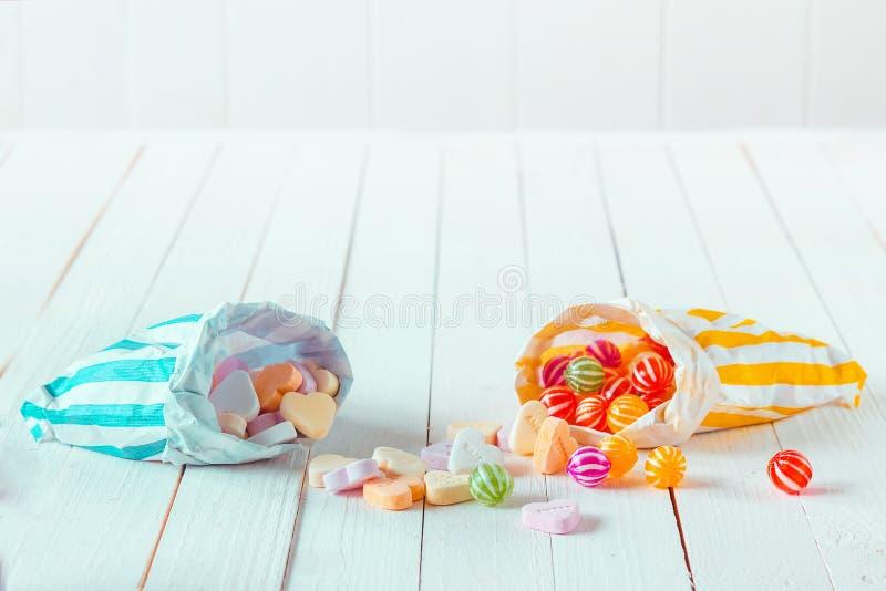 Zusammenstellung von Süßigkeiten in zwei Taschen über einer Tabelle lizenzfreie stockbilder