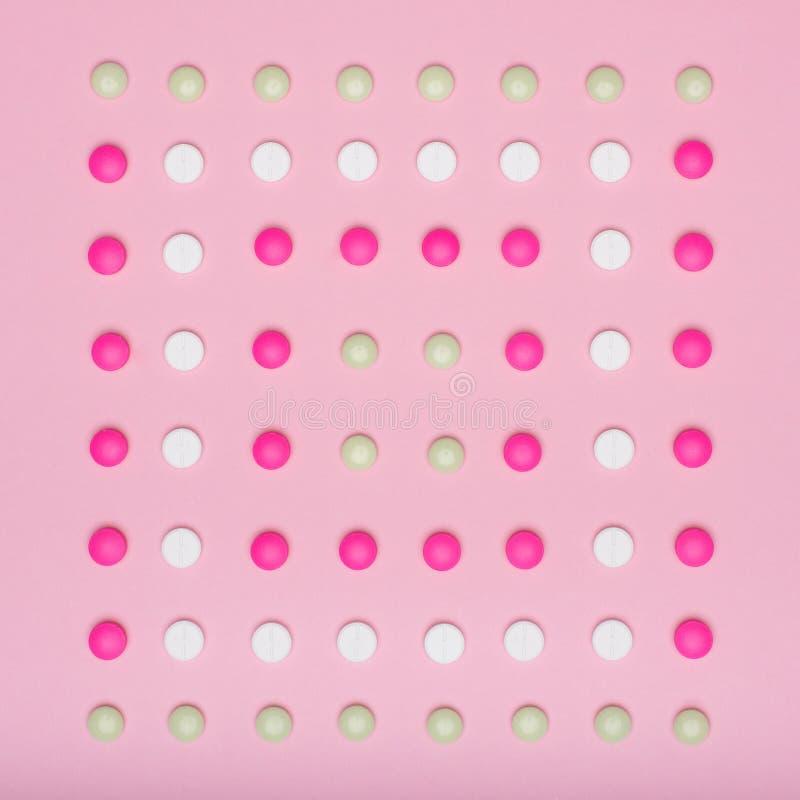 Zusammenstellung von verschiedenen bunten Pillen in Folge, auf rosa Pastell farbigem Hintergrund Medikations- und Verordnungspill stock abbildung