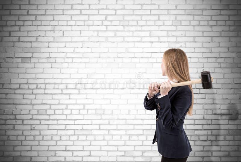 Zusammenstoßende weiße Backsteinmauer der Frau mit Vorschlaghammer lizenzfreie stockfotos