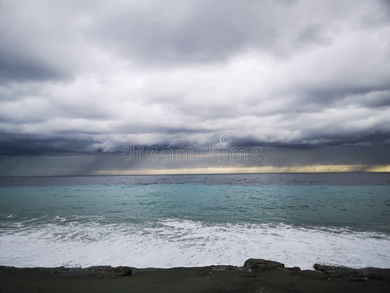 Zusammenstoßende Wellen auf Strand mit Sturmwolken stockfotografie