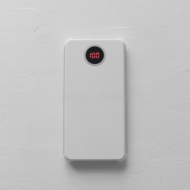 Zusatz für Ihr Telefon: Machtbank für einen weißen Smartphone mit einem Vorwurfs-Sensor auf einer Draufsicht des weißen strukture lizenzfreie stockfotos