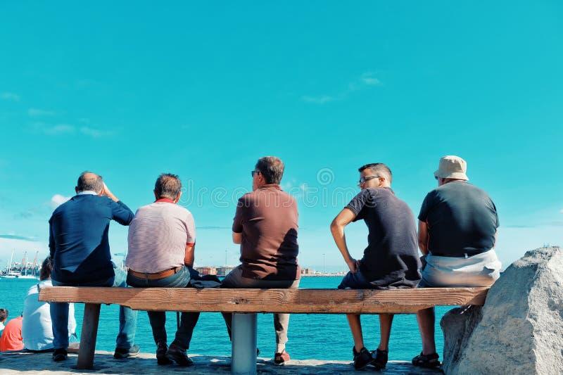 Zuschauer drängen die Leute, die auf einer Bank sitzen, um den Atlantik-Überfahrtsegelboots-Regattarennen-BOGEN 2018 aufzupassen lizenzfreie stockfotos