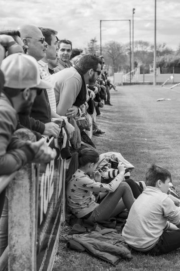 Zuschauer passen ein Rugbymatch auf der Seite des Feldes einer kleine französische Stadt auf stockbilder