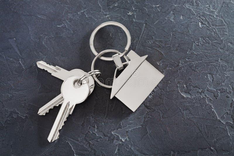 Zustandskonzept mit Schlüssel, keychain mit Haussymbol, Steinhintergrund lizenzfreie stockfotos