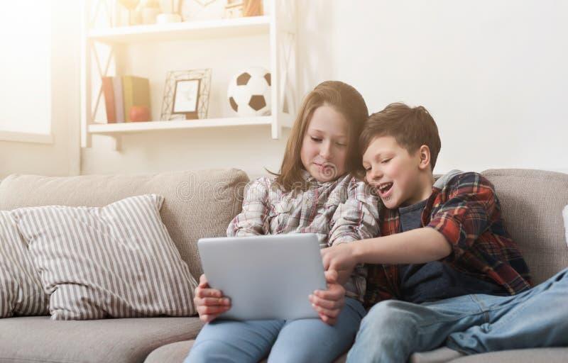 Zuster en broer het letten op film op digitale tablet thuis stock afbeelding