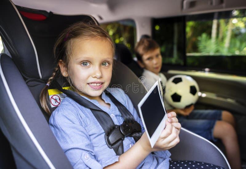 Zuster en broer het spelen met digitale apparaten in de auto royalty-vrije stock afbeelding