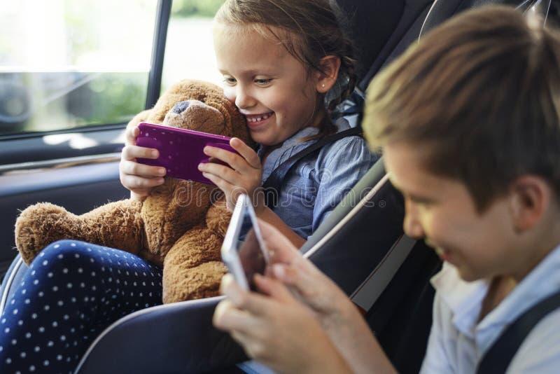Zuster en broer het spelen met digitale apparaten in de auto stock afbeelding