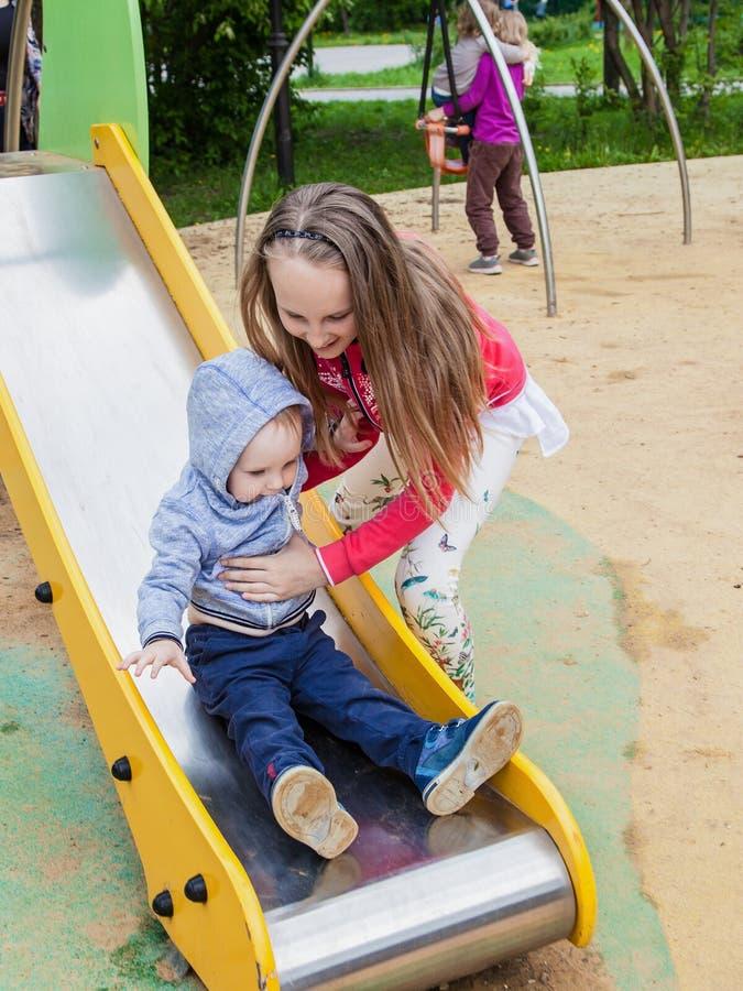 Zuster en broer het spelen op Playgrou Het meisje helpt een kleine jongen op een kinderen` s dia stock afbeeldingen