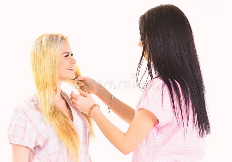 Zusters, beste vrienden die in pyjama's vlecht, kapsel maken elkaar Blonde, brunette op het glimlachen gezichten in kleren voor s stock afbeeldingen