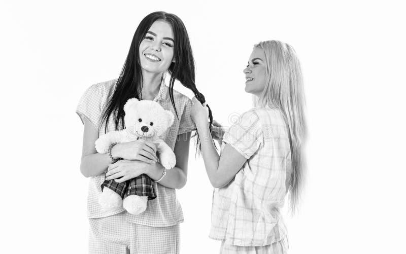 Zusters, beste vrienden die in pyjama's vlecht, kapsel maken elkaar Meisjes in roze pyjama's, geïsoleerde witte achtergrond royalty-vrije stock foto