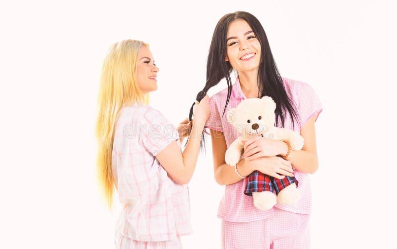 Zusters, beste vrienden die in pyjama's vlecht, kapsel maken elkaar Meisjes in roze pyjama's, geïsoleerde witte achtergrond royalty-vrije stock afbeeldingen