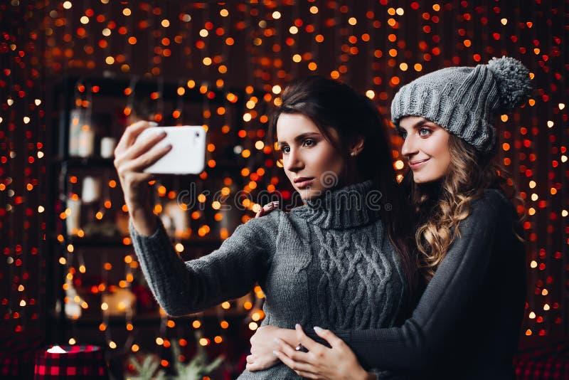 Zusters die elkaar omhelzen en zelfportret nemen bij smartphone royalty-vrije stock foto's